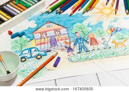 Hand drawn Bright Childrens Sketch With Happy Family, House, Dog, Car on the Lawn with Flowers with lying pencils and pastel - concept of children creativity, close up perspective view