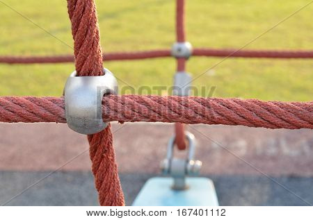 Red rope knot line tied together in the playground,as a symbol for harmony, teamwork, solidarity or collaboration.