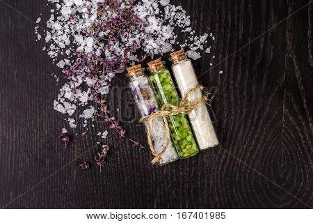 Glass jar with bath salts on black background. Top view. Still life