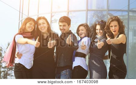 A group of college students smiling friendly standing next to each other with arms extended forward and the thumbs up on a sunny day