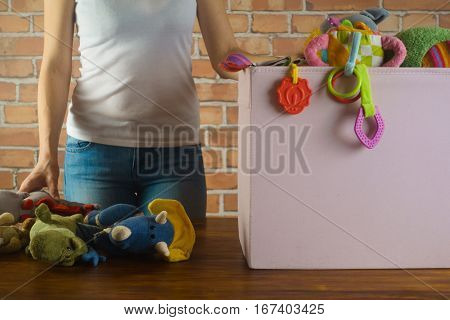 Young girl with toys and box prepare to donate it