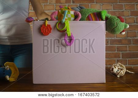 Charity store. Yong girl sorting used toys which donated to her