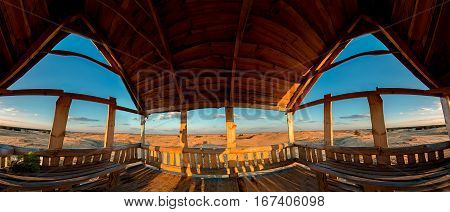 Wooden lookout alcove overlooking the sandy desert. Evening in the late autumn. View from inside.