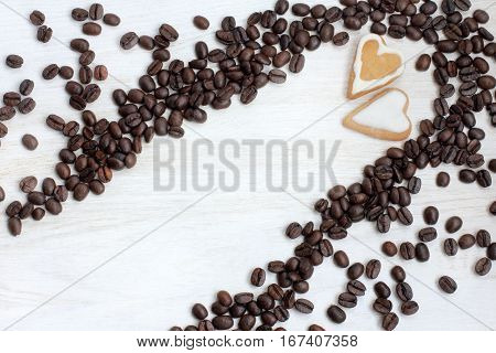 couple cookies in the shape of heart in coffee beans scattered on the table top view / date with gusto
