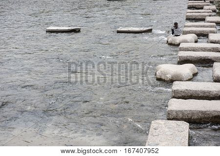We can seen a girl sitting on a big block of a stone on the water. We can also see how these big blocks are controlling the water flows of a river is seen in the picture.