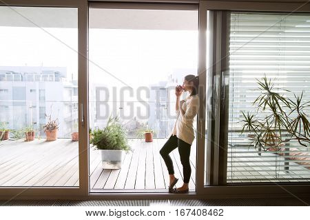 Beautiful young woman relaxing on balcony with city view holding cup of coffee or tea, drinking from it