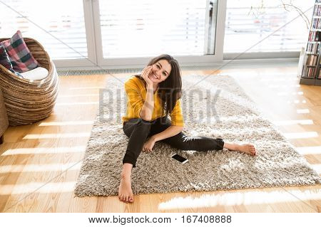 Beautiful young happy woman at home sitting on carpet, smart phone laid next to her