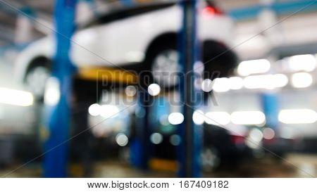 Automobile service - mechanics checking lifted car, de-focused, wide angle