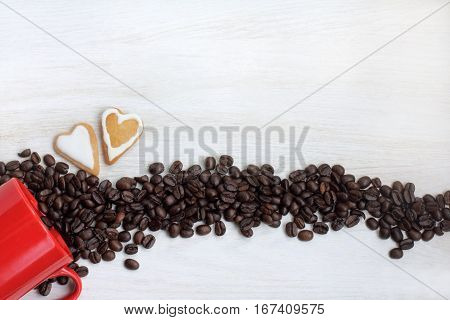 couple cookies in the shape of hearts and spills beans on the table top view / romantic date with coffee aroma