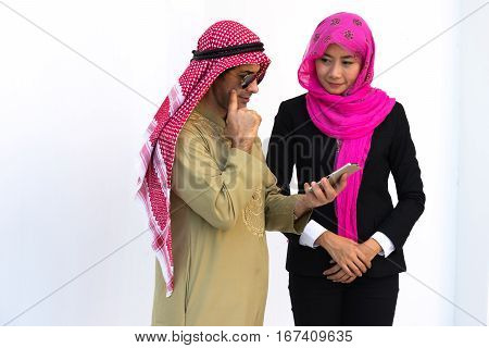 Businesswoman in black suit wearing pink turban looking middle eastern man who is thinking about ordering goods over the mobile phone on white background.