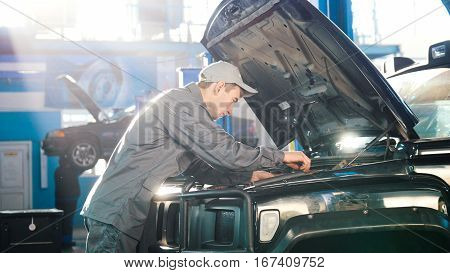 Mechanic in car service - compartment for luxury SUV, wide angle