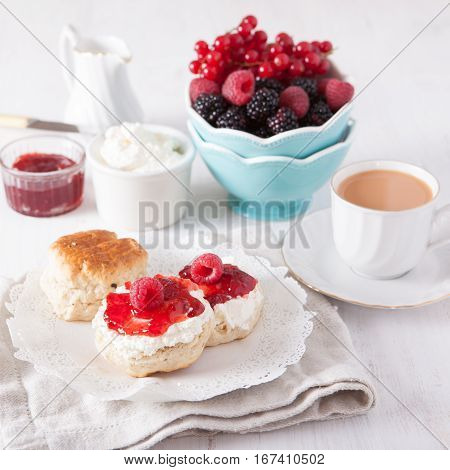 Traditional English cream teas: scones with clotted cream and raspberry jam with berries, selective focus