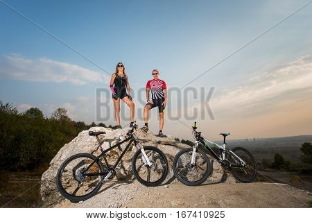 Cyclist Couple In The Sunglasses Standing On A Rock
