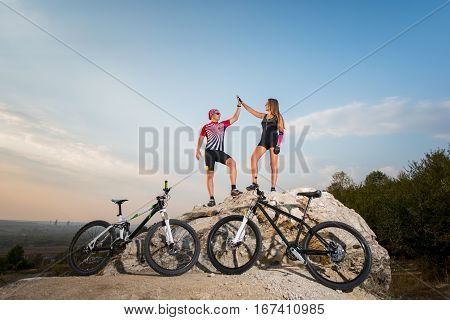 Biker Couple Standing On A Rock And Giving High Five