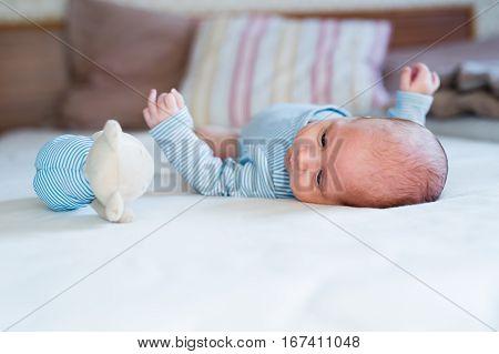 Cute newborn baby boy in blue striped onesie lying on bed, teddy bear toy next to him