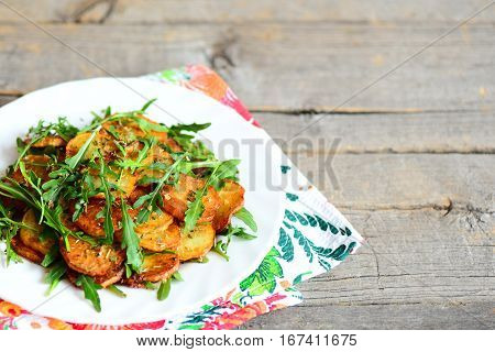 Warm potato arugula salad on a plate. Pan-fried sliced potatoes with fresh arugula and spices. Wooden background with empty place for text. Rustic style