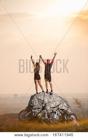 Cyclists Standing On A Large Stone Near Mountain Bikes
