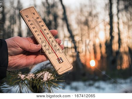 Thermometer in hand in the winter forest at sunset