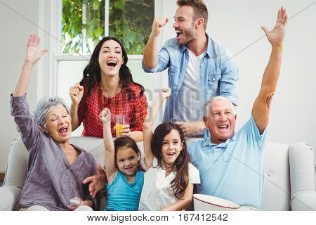 Multi generation family on sofa cheering while watching television at home