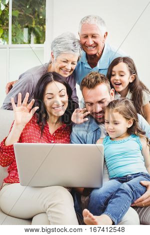 Happy multi generation family using laptop at home