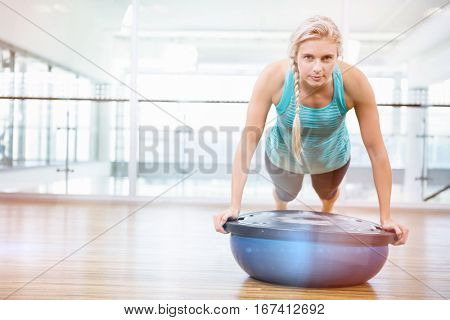 Portrait of fit woman doing push up on bosu ball in fitness studio