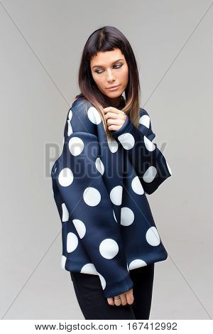 Nice thoughtful model close-up looking aside in studio with grey background, she is wearing dark blue polka dots costume, her head is slented and eyes are looking aside
