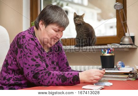 Mentally Disabled Woman Playing Cards, Therapeutic At Everyday Life