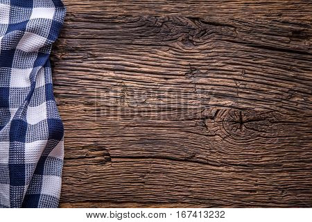 Top view of checkered tablecloth or napkin on empty wooden table.
