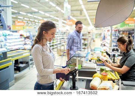 shopping, sale, consumerism and people concept - happy couple buying food at grocery store or supermarket cash register and swiping customer card