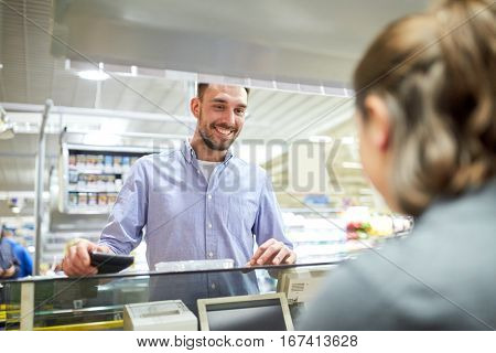 shopping, sale, consumerism and people concept - happy man with wallet at grocery store or supermarket cash register