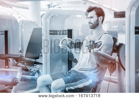 Focused man using weights machine for arms at gym