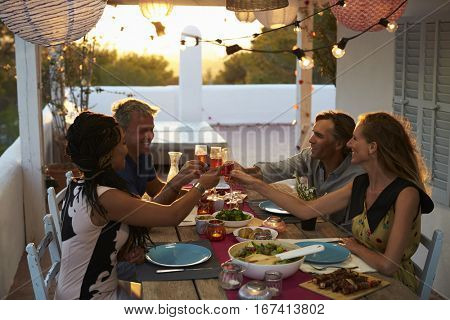 Two couples making a toast at dinner on a rooftop terrace