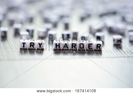 Try harder inspirational advice spelled by tiled letter beads