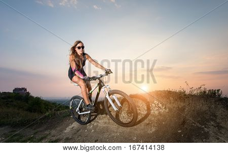 Pretty Woman Riding On The Mountain Bicycle Against Evening Sky
