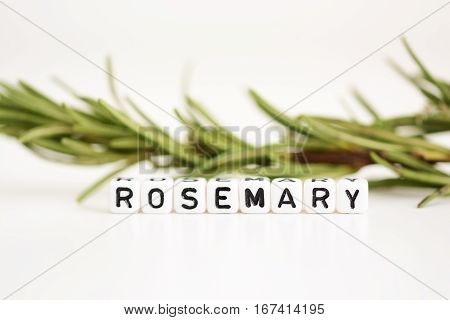 Blurred branch of rosemary in the background with close-up on plastic letter beads spelling