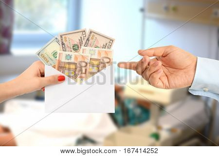 Woman bribing a man with an envelope full of money in a hospital suggesting a corrupt healthcare system