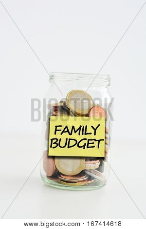 Isolated glass jar with family savings label filled with coins