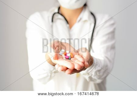 Cropped shot of a female doctor displaying a handful of tablets and pills in her palm