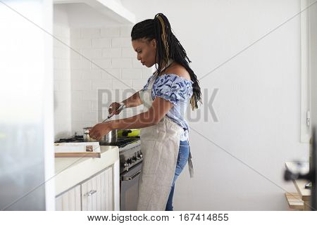 Woman cooking with a saucepan on the hob in her kitchen