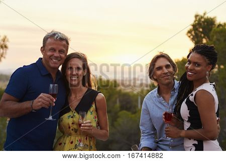 Two happy adult couples socialising outdoors look to camera