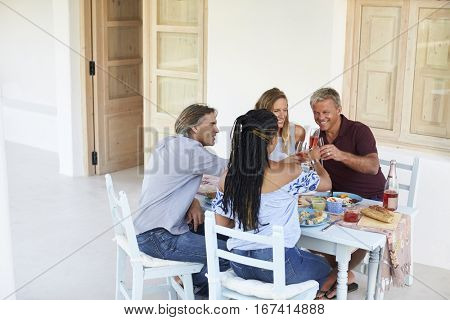 Two couples at dinner on a patio make a toast, back view