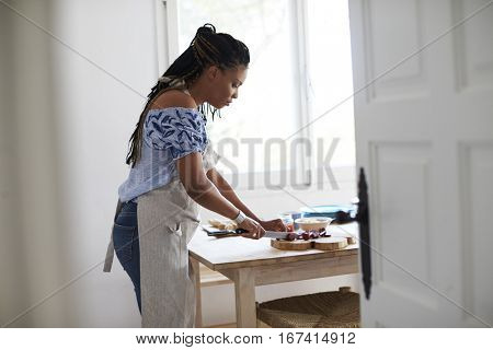 View from doorway of woman chopping food on kitchen table