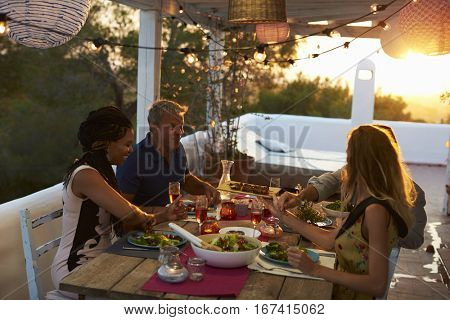 Two couples eating dinner at sunset on a rooftop terrace