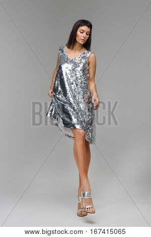 Beautiful model looking downand flirting in grey background studio wearing silver short dress and brilliant shoes. Her long legs are perfect