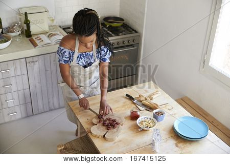 Elevated view of woman chopping ingredients at kitchen table