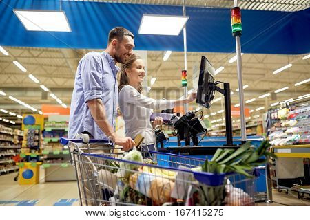 shopping, sale, payment, consumerism and people concept - happy couple with credit card buying food at grocery store or supermarket self-service cash register