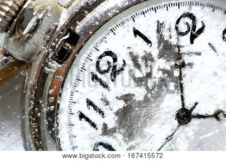 Close-up of pocket watch under frozen water background with ice