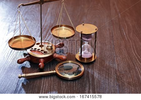 Vintage still life. Weight scale and hourglass near magnifying glass on wooden table