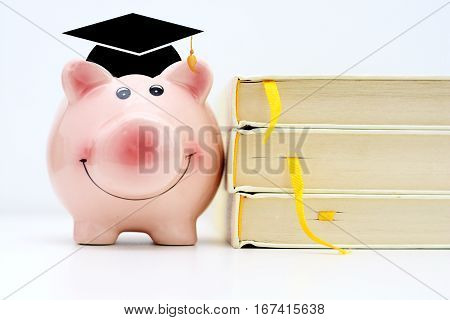 Piggy bank wearing a graduate cap standing near a pile of books. Saving for higher education concept