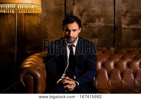 Rich businessman sitting quiet on sofa in restaurant.. Handsome luxury man having secret concerning mafia. Wealth, luxury concepts.